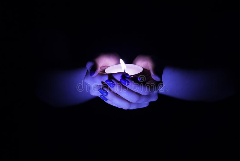 Candle in hands stock photo