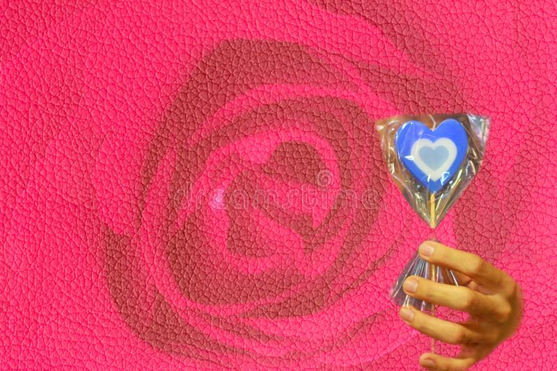 Candle heart-shaped with three tone as blue,white and light-blue on stick in hand On the Leather Pink Roses texture . royalty free stock images