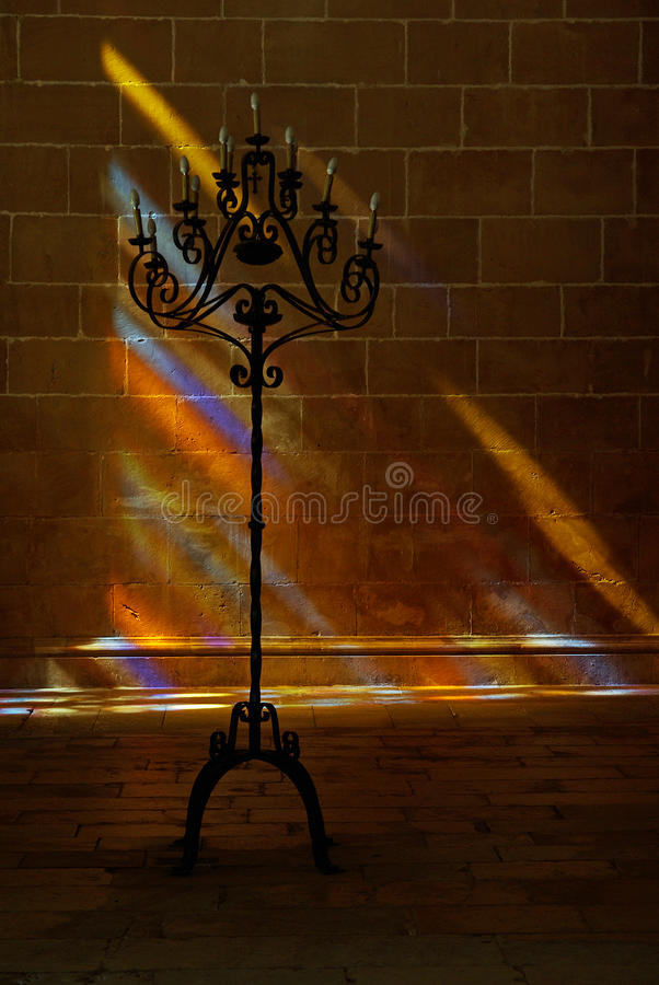 Candle Holder. A large candle holder taken against a stone wall of Batalha monastery. The wall is lit by colourful lights cast through a stained glass window stock photo