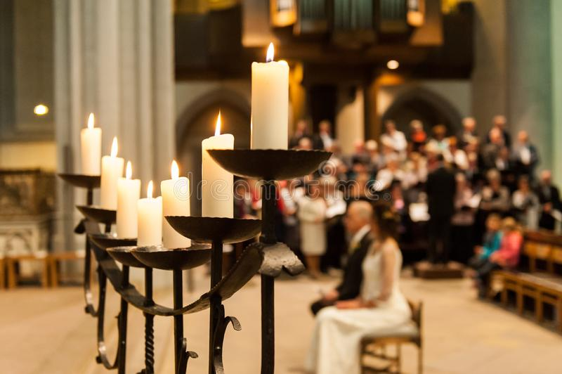 Candle holder with candles and blurred people in church. On wedding day stock image
