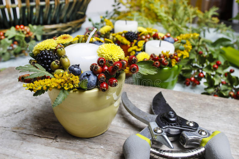 Candle holder decorated with autumn flowers. And other plants. Making floral decorations at florist workshop royalty free stock image