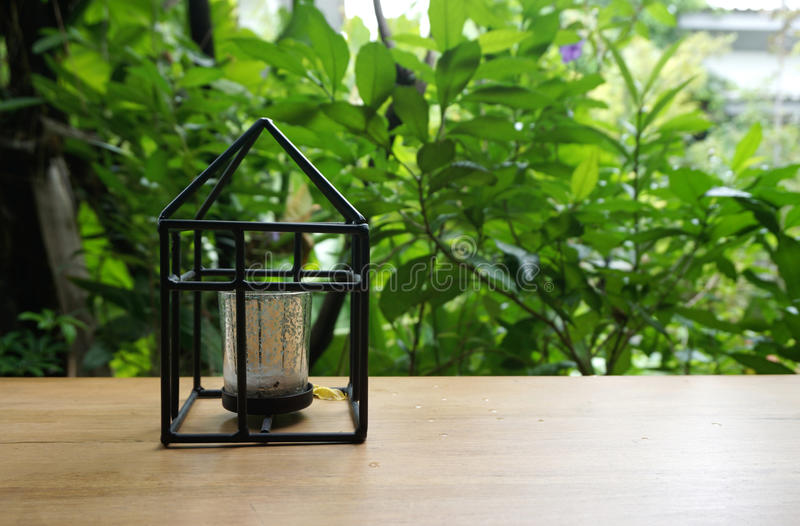 Candle holder in house shape with nature background. Black frame Candle holder in house shape onthe timber table with nature background royalty free stock photography