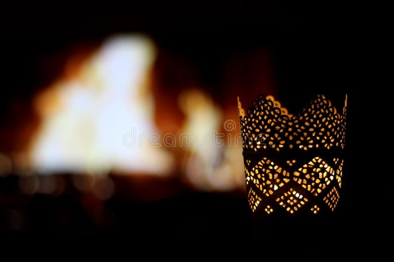 Candle Holder. Intricate candle holder with lit candle, in front of a fireplace. Selective focus stock photos
