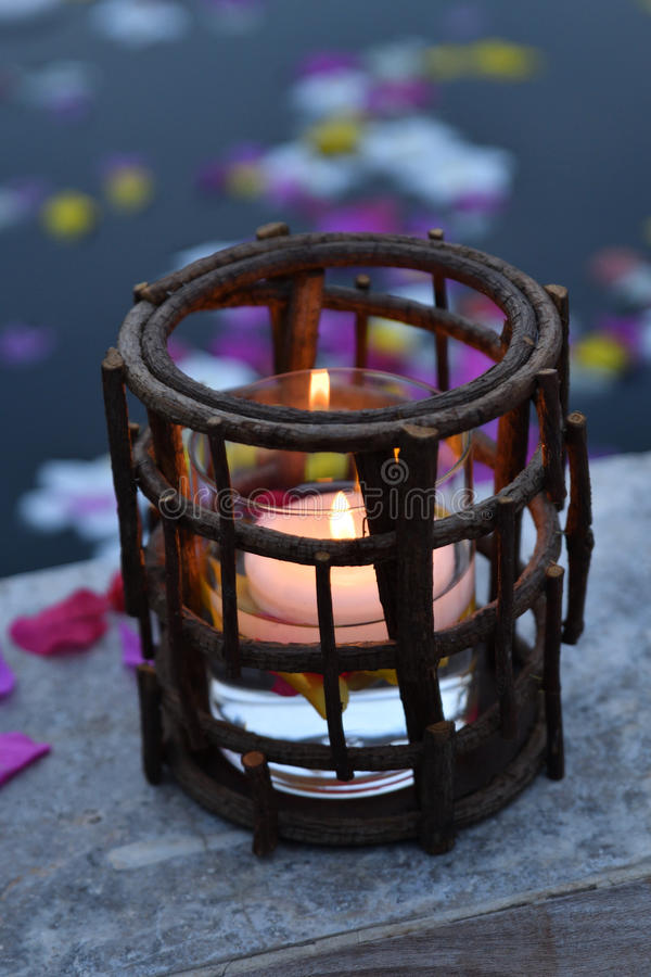 Candle in holder by pool royalty free stock photography