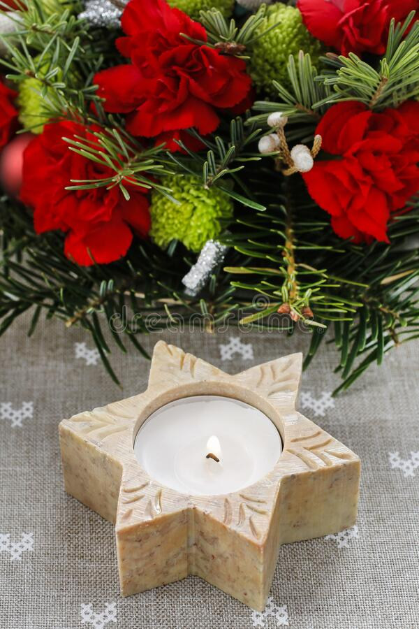 Candle holder in star shape in front of floral christmas decoration. Festive decor stock photography