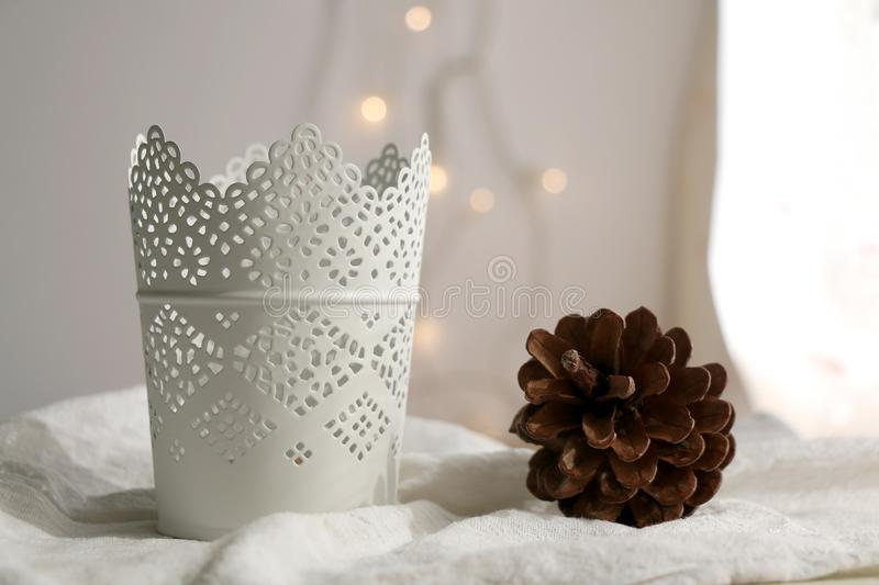 Candle Holder. White candle holder and pine cone. Fairy lights in the background, Selective focus stock images