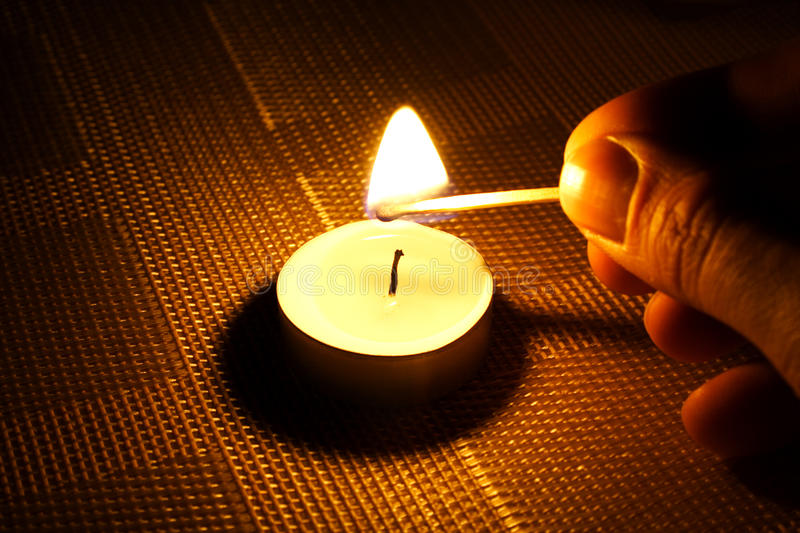 Candle ignition with match royalty free stock photography