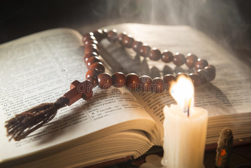Candle with incense and holy book. Composition of candle with incense and holy book stock images
