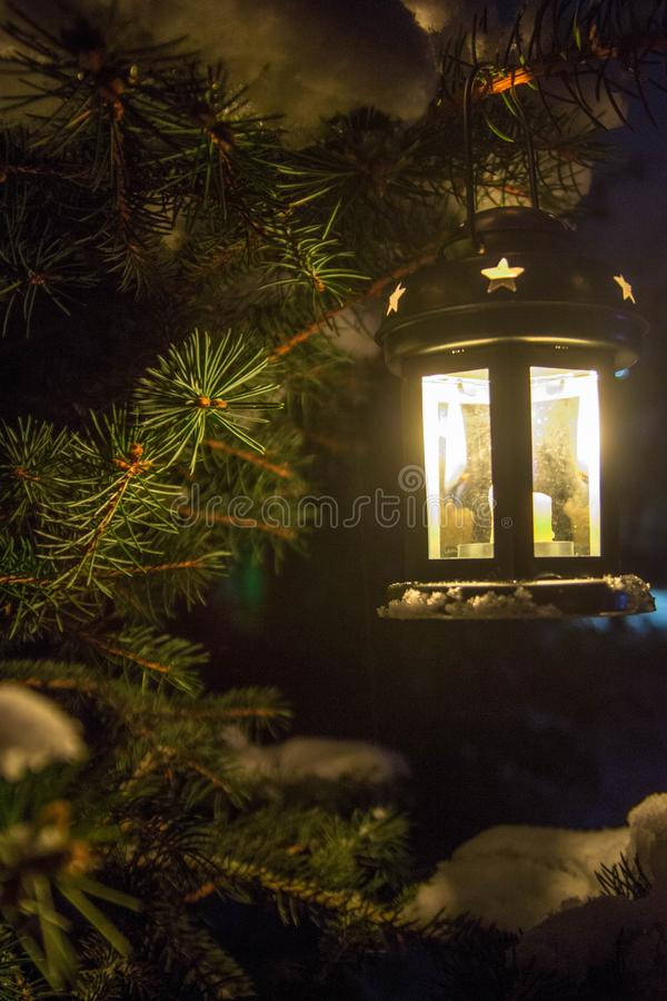 A candle in the lantern illuminates the winter night. stock image