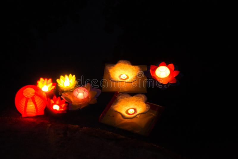 Candle lanterns floating on a river among colorful reflections during night royalty free stock photo