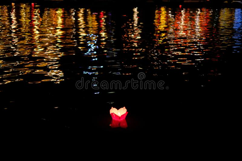 Candle lanterns floating on a river among colorful reflections during night in Hoi An, Vietnam royalty free stock images