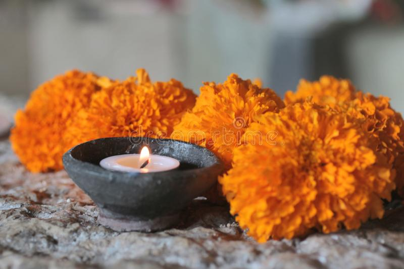 Spirituality, SPA and self therapy concept. Candle light in a natural ceramic bowl and marigold flowers. stock image