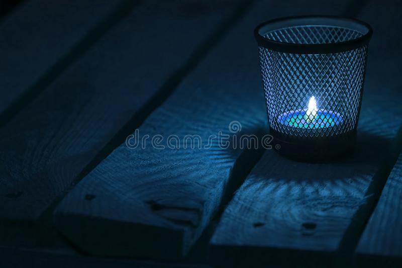 Tealight on wooden background. Candle light on natural wooden background. Blue tealight. Cold mood. Soft focus stock photo