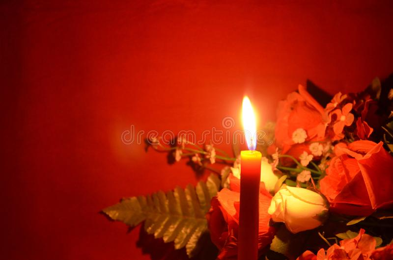 Candle light and roses on red background royalty free stock images