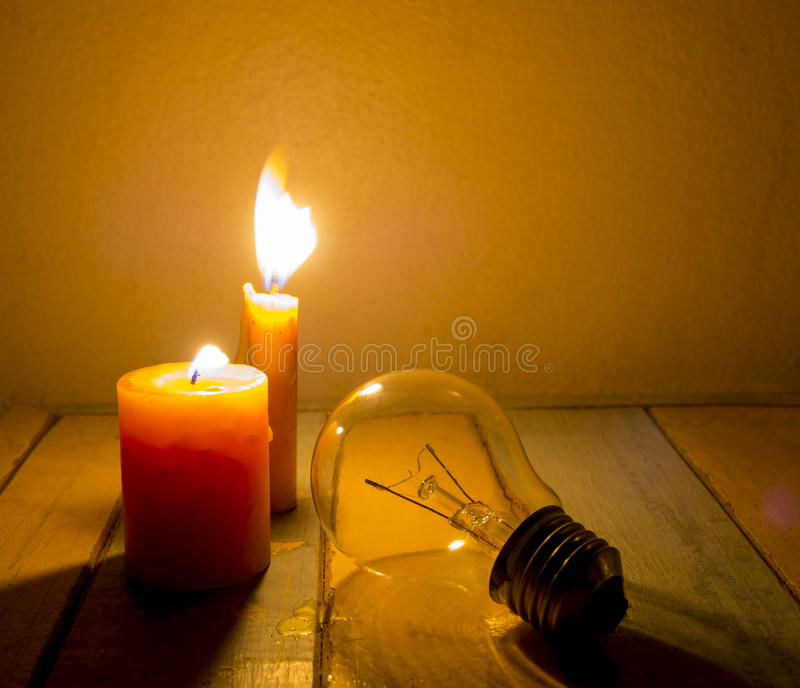 Candle light shine on incandescent bulb. No electricity makes electrical equipment useless royalty free stock photos