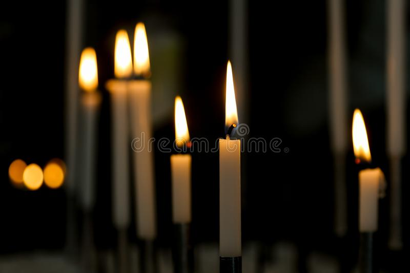 Burning Candle lights with dark background. Candle lights in a Church in The Netherlands. Candle with golden flame burning for hope royalty free stock photography