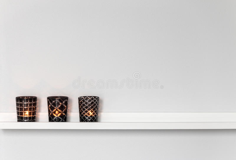Candle lights on white shelf. Home decor, candle lights on a white shelf royalty free stock photo
