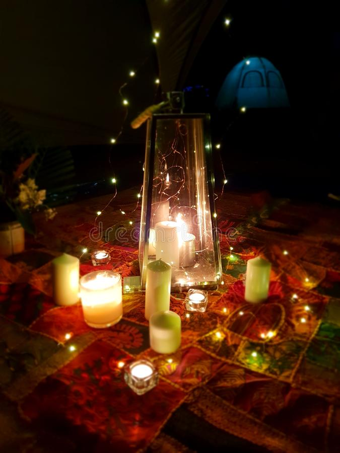 Candle lit candlelit camping picnic blanket under moonlight. A decorative display on a camping trip stock photography