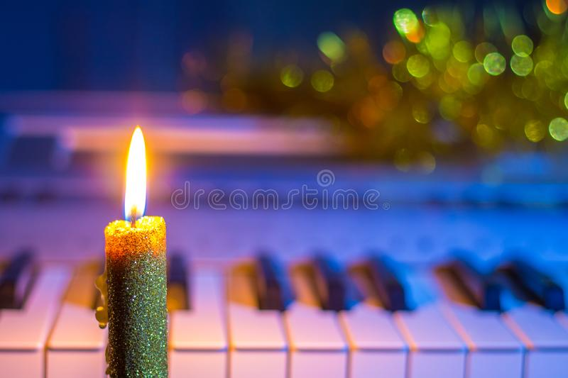 Candle near the piano, which is decorated with Christmas shiny garlands. Music on New Year`s night_ stock photography