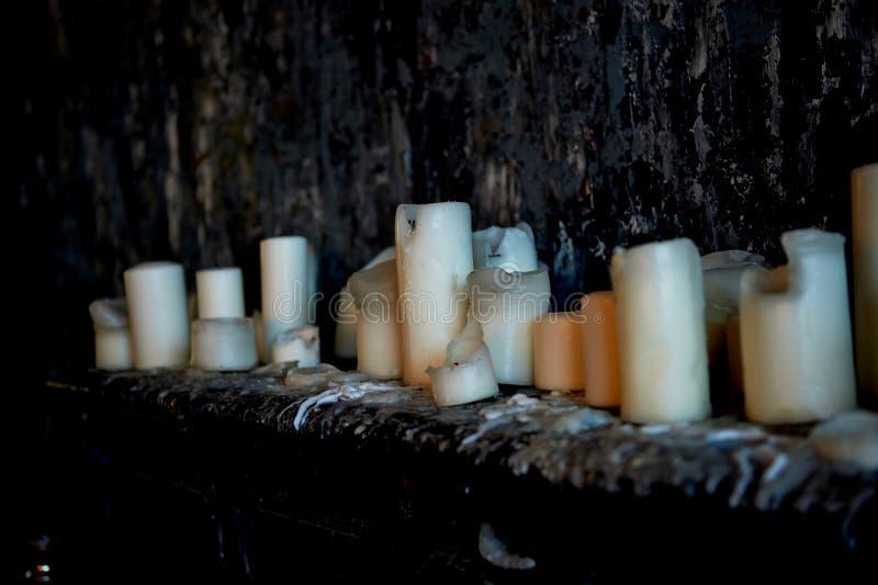 Candle o suporte em uma superfície escura contra uma parede escura, tudo na cera empapado Muitas velas, o fogo são iluminadas ext fotos de stock