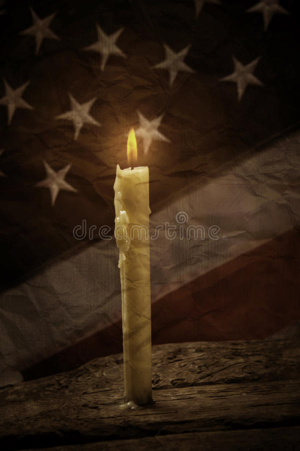 Candle and old american flag. Burning candle on wooden surface. Light will show the way. Peace is a priceless treasure stock image