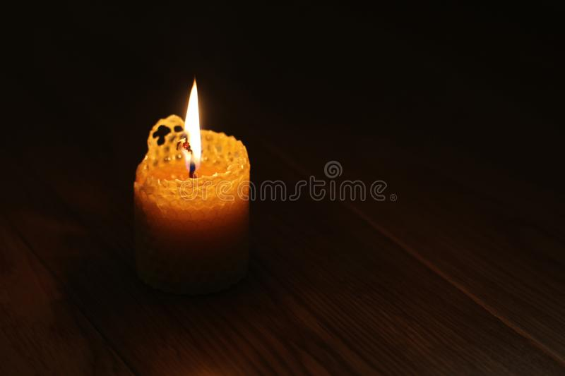 Candle, one candle flame at night closeup on a black background. Orange candle in the dark. Copy space royalty free stock images