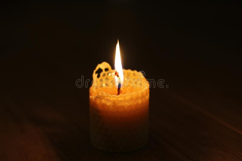 Candle, one candle flame at night closeup on a black background. Orange candle in the dark. Copy space stock photos