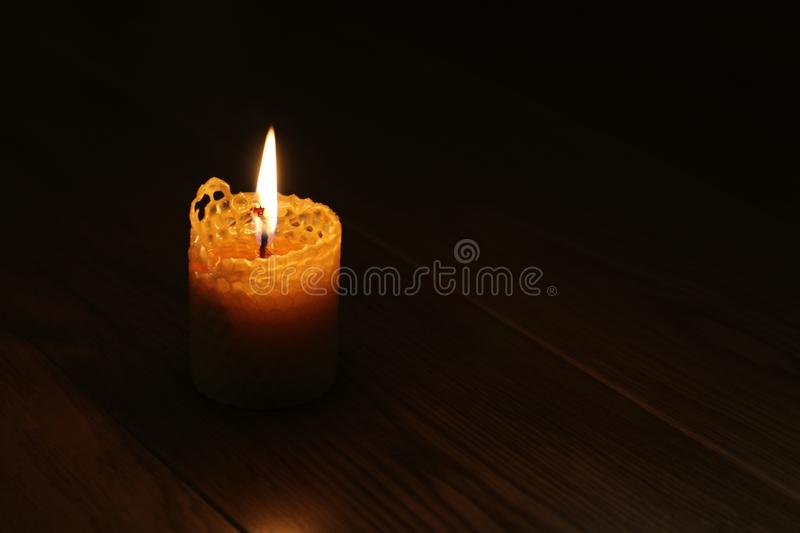 Candle, one candle flame at night closeup on a black background. Orange candle in the dark. Copy space.  stock photos