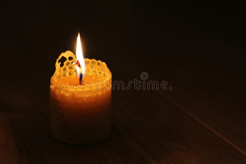 Candle, one candle flame at night closeup on a black background. Orange candle in the dark. Copy space.  royalty free stock photo