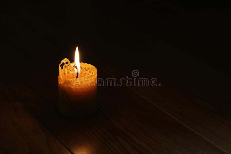 Candle, one candle flame at night closeup on a black background. Orange candle in the dark. Copy space.  royalty free stock photography