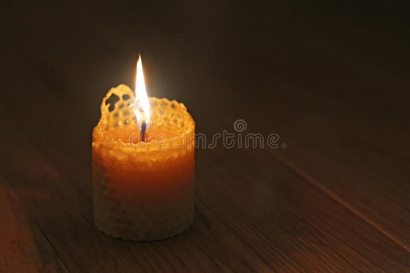 Candle, one candle flame at night closeup on a black background. Orange candle in the dark. Copy space.  stock photo