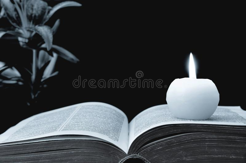 Candle, opened book and flowers on black background royalty free stock photos