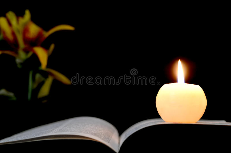 Candle, opened book and flowers isolated on black. Background stock photography