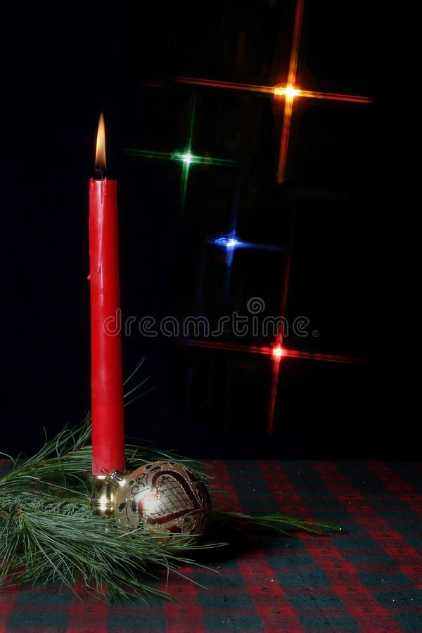 Candle and ornament on holiday tablecloth stock images