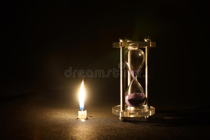 Candle and sand. Finished dousing the burning candles and the hourglass represents the time passed quickly, need to treasure royalty free stock photography