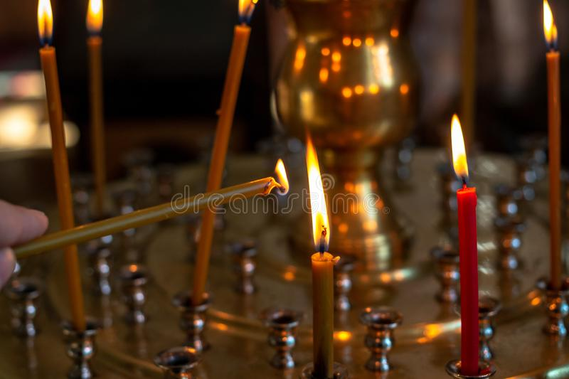 The candle is set on fire. Candles burn in the church on a special stand. stock images