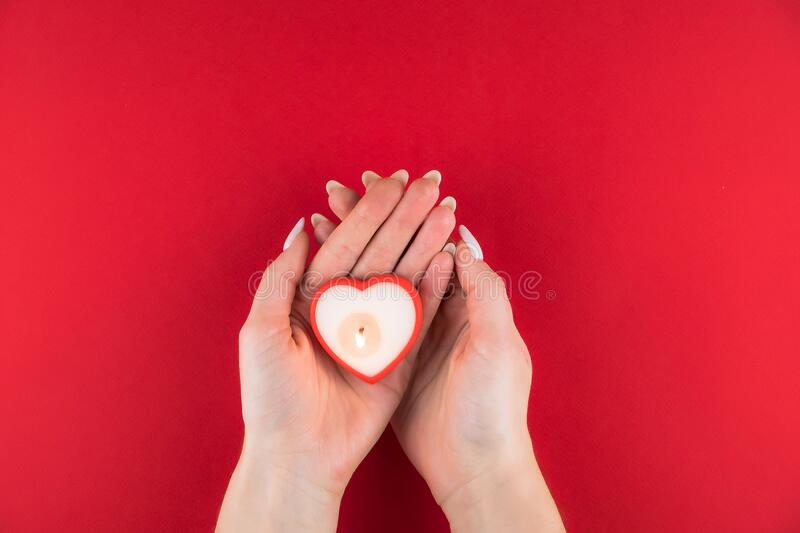 Candle in the shape of a heart in the hands of woman on red background for Valentines day. Candle in the shape of a heart in the hands of woman on red stock photo