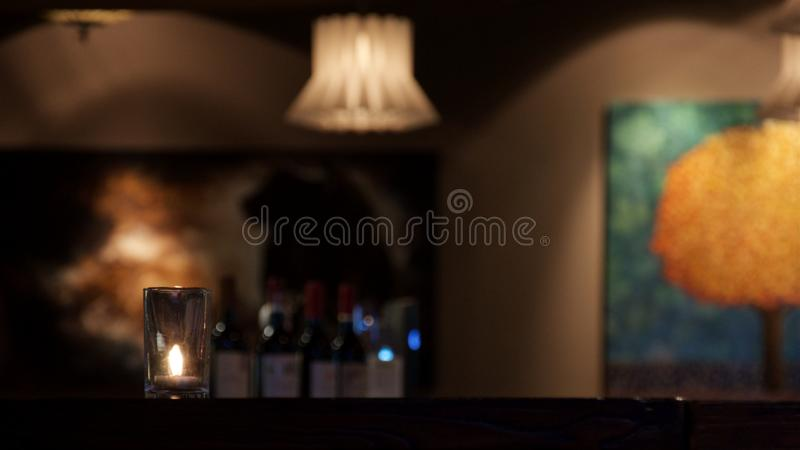 The candle stands on the table in the muffled light in the restaurant royalty free stock photo
