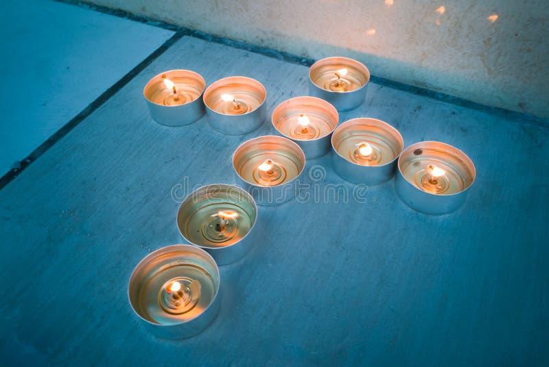 Candle tea lights in Christian crucifix cross formation. Glowing candle tea lights in Christian crucifix cross formation stock image