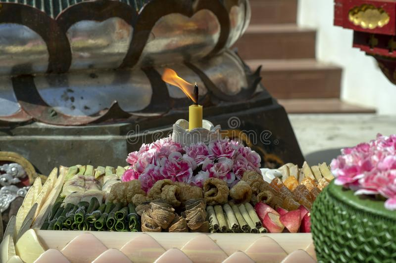 Candle and offerings at Wat Ming Mueang, Chiang Rai, Thailand. Candle and votive offerings at Wat Ming Mueang, Chiang Rai, Thailand stock images