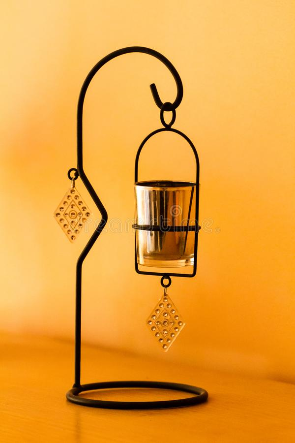 Simple candleholder. Candleholder on the tabel, yellow wall stock photos