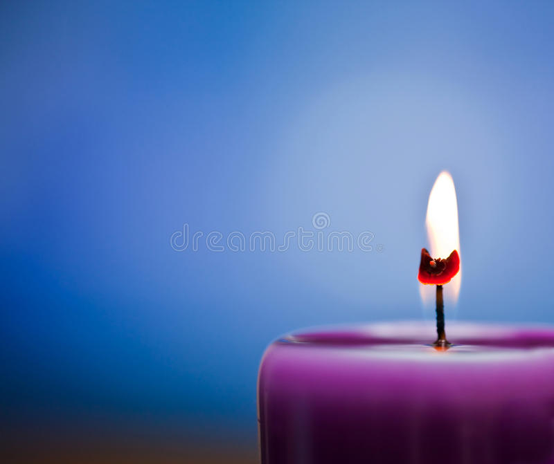 Candlelight. Purple candlelight on a blue background royalty free stock image