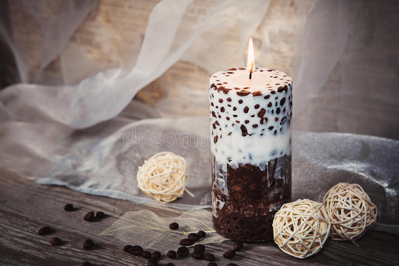 Candlelight. Beautiful handmade candle and whiteTwig Balls on old wooden texture background. Decorative Handmade candle with coffee beans. Candlelight. Beautiful stock photo