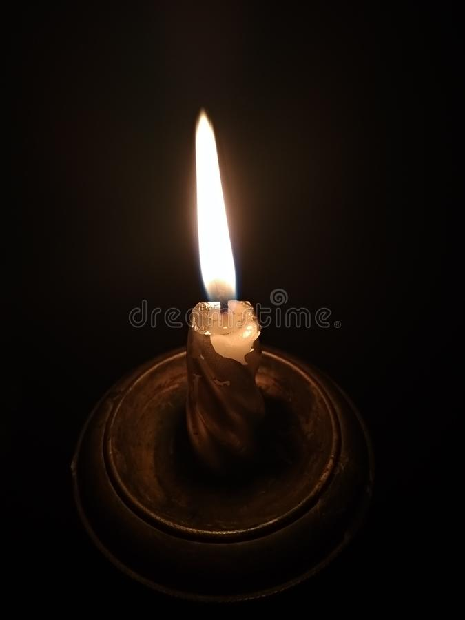 Burning candle in a candlestick on a black background stock photo