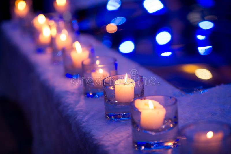 Candlelight. With defocussed lights in the background, and golden tinsel. Perfect Christmas decoration royalty free stock photo