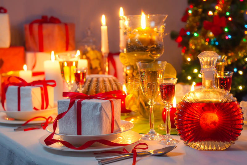 Candlelight and gifts all around the Christmas table. Closeup of candlelight and gifts all around the Christmas table stock photo