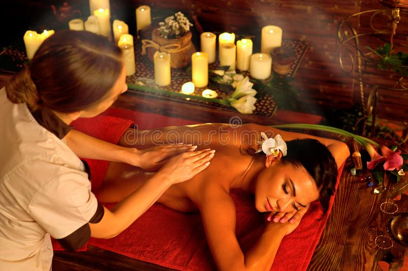 Candlelight massage. Of women with masseuse with sun flare royalty free stock photography