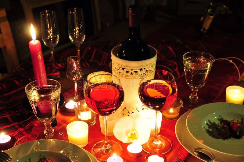 candlelightmatställerött vin arkivfoton