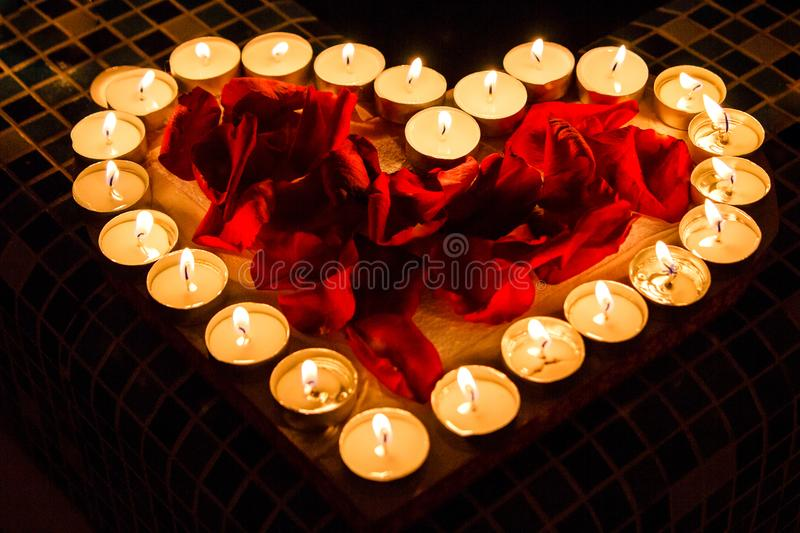 Candlelights shine in form of the heart with red roses petals. On the border of waterpool. Love adn romantic royalty free stock image