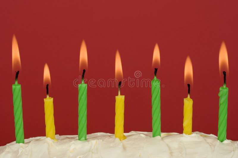 Candles. Green and yellow candles on a butter icing cake with bright red background stock photo